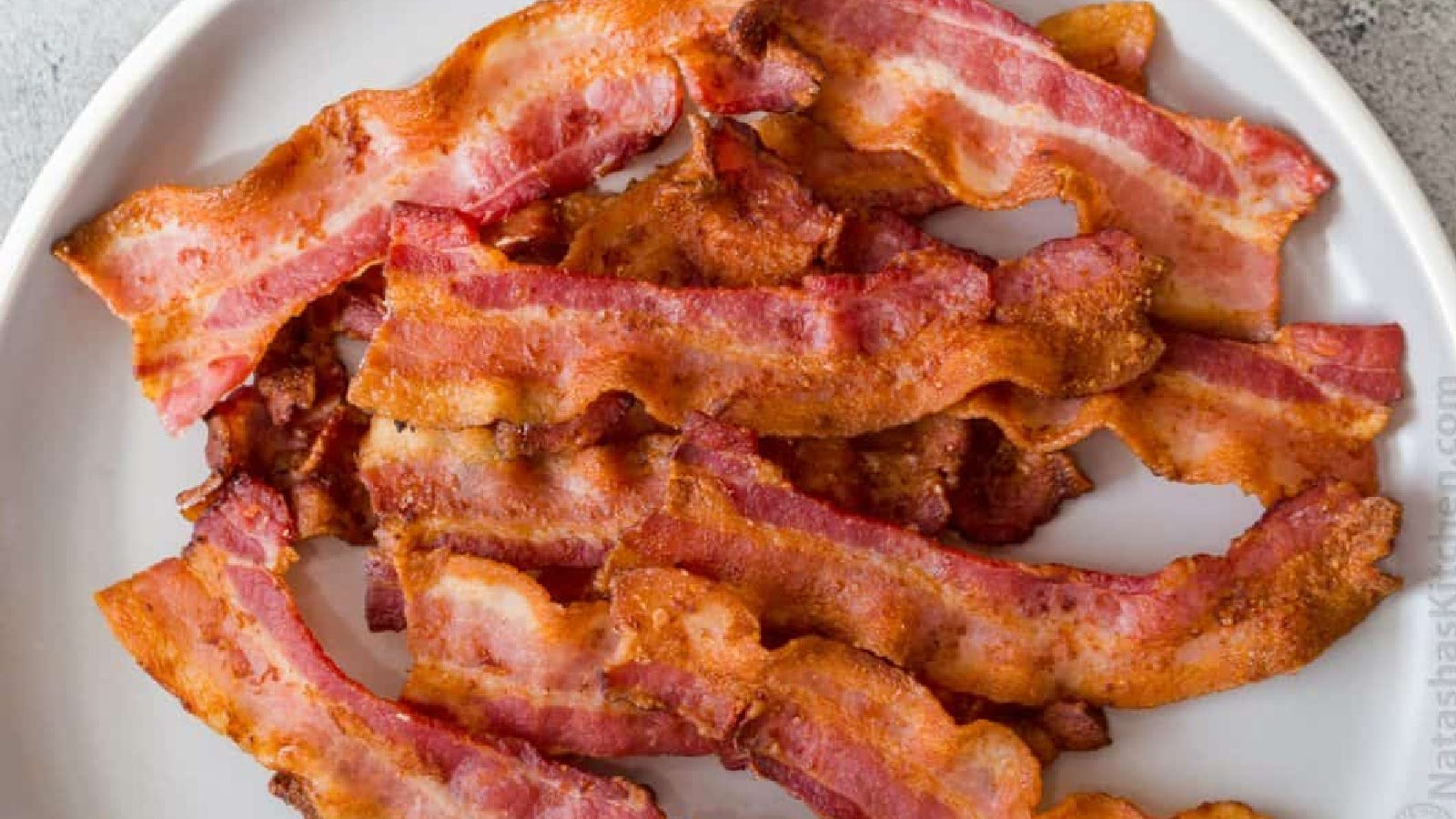 A white plate full of juicy and crispy slices of air fried bacon.