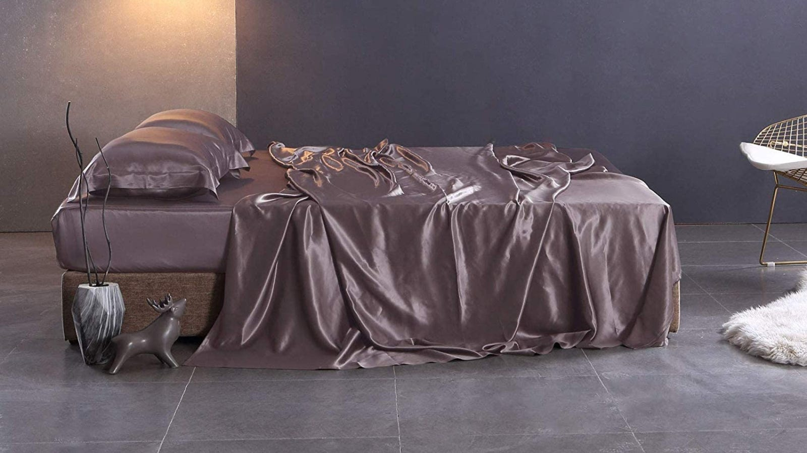 A bed with dark purple silk sheets and matching pillows sitting in a dark room.