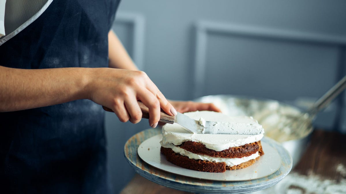 A woman icing a cake.