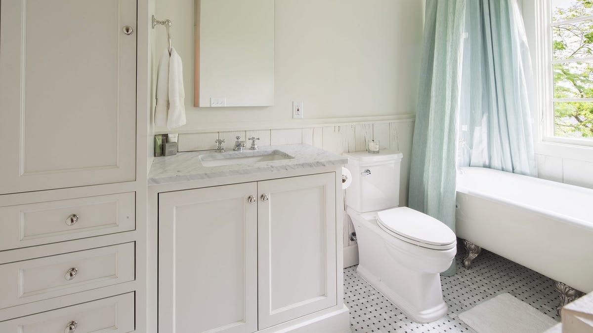 A sunny bathroom with a fresh clean shower curtain and new bath mat.