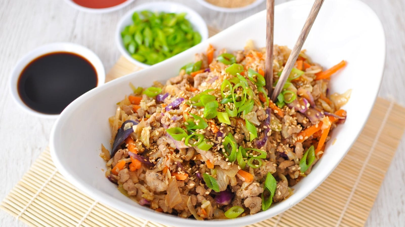 A beautiful oval serving dish filled with egg roll in a bowl, topped with sesame seeds and chopped green onions, with a bowl of soy sauce and green onions on the side.