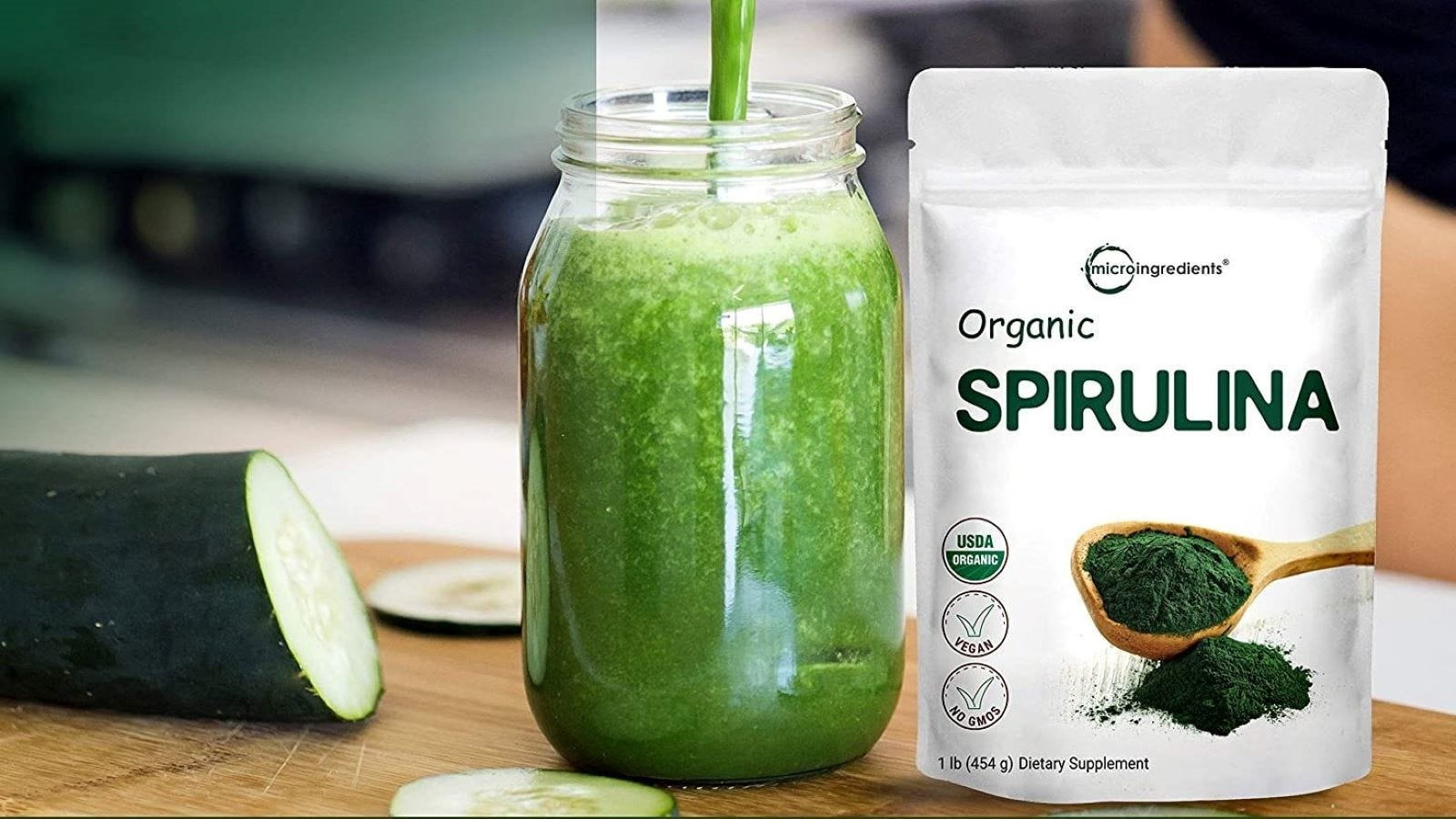 A sliced cucumber sitting next to a green smoothie in a jar and a package of Spirulina.
