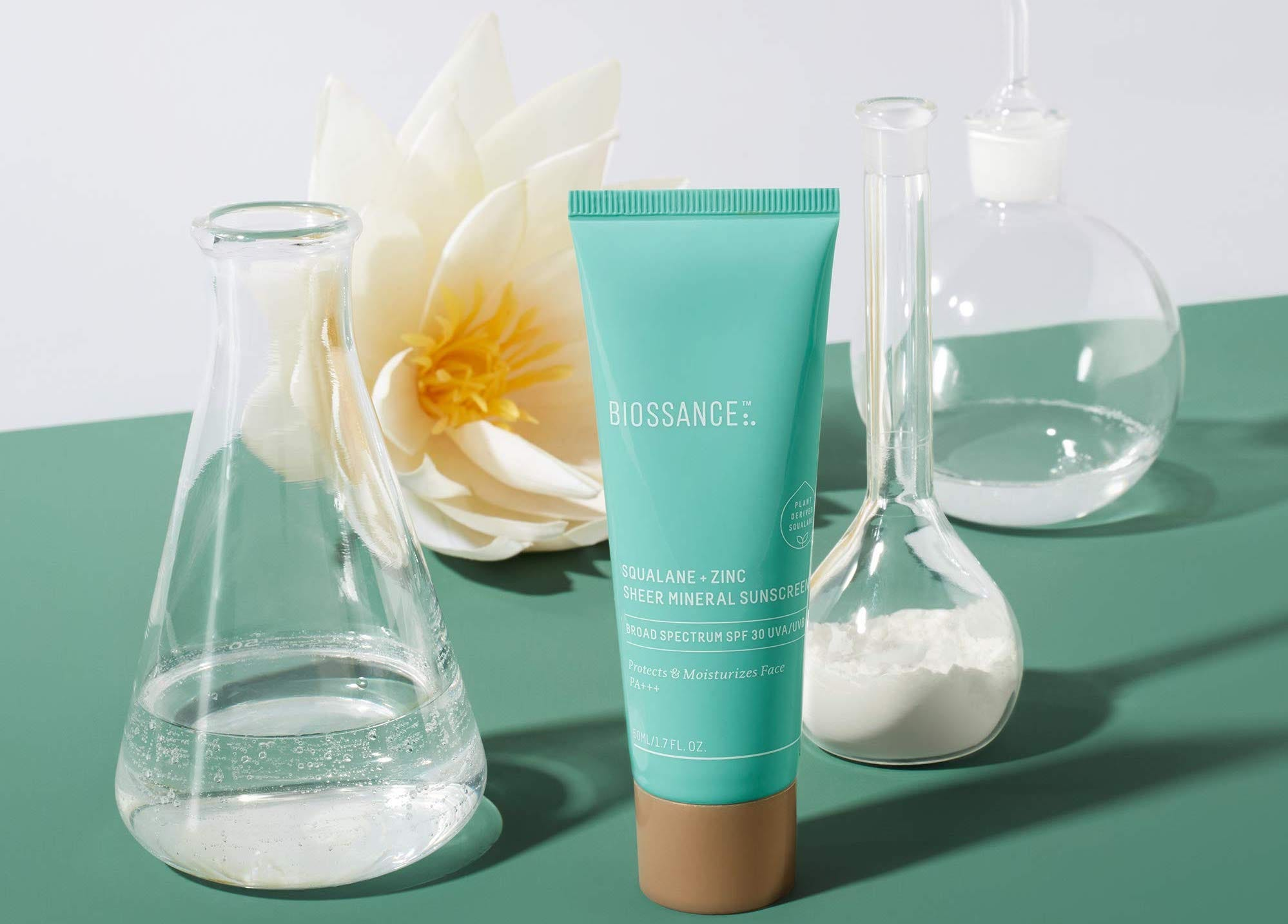 A green tube of sunscreen on a green counter with glass chemistry flasks next to it