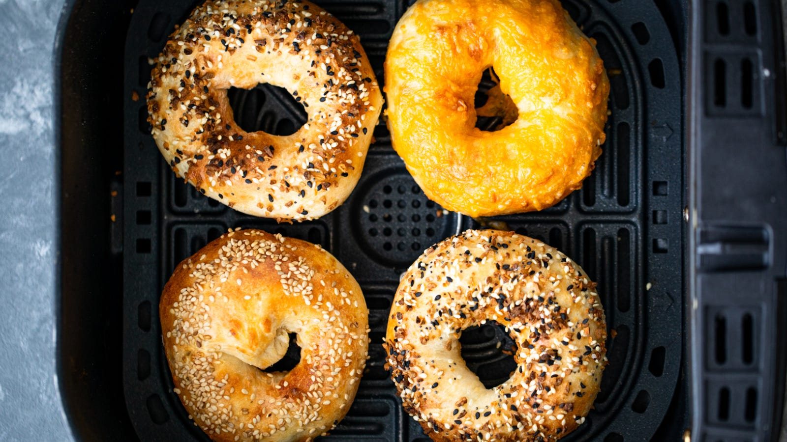 A large capacity air fryer compartment filled with four separate homemade bagels, each topped with different seasoning toppings.