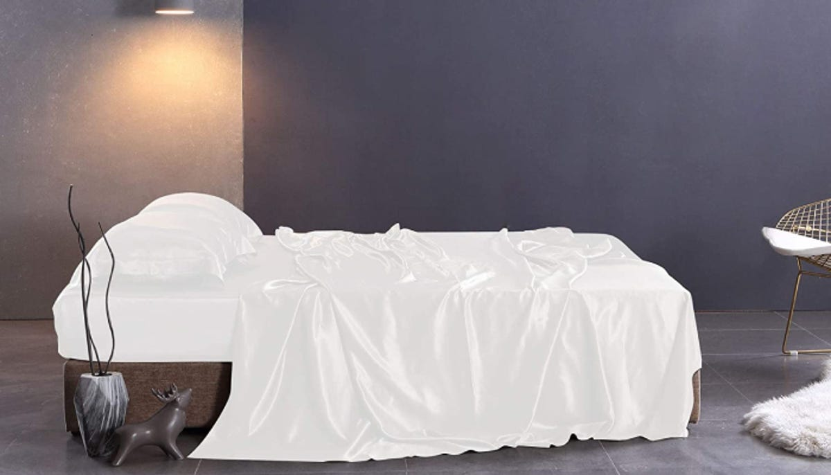 a bed with white satin sheets on it in a room with purple walls and modern decor