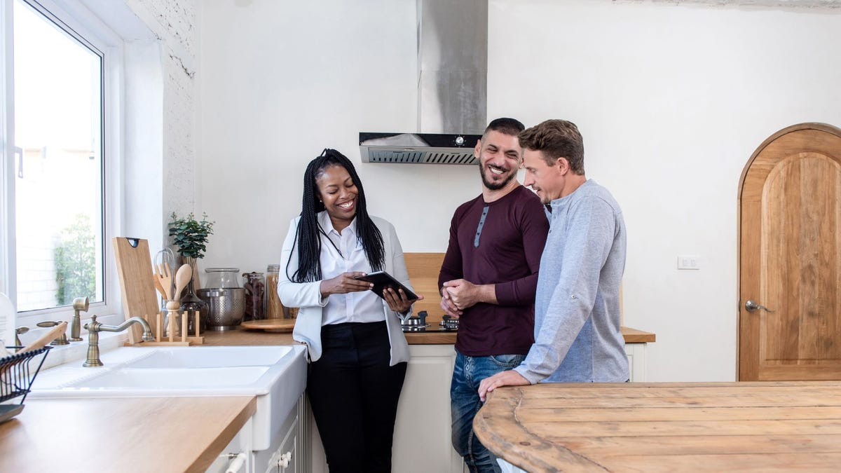 A realtor showing a home to a male couple.
