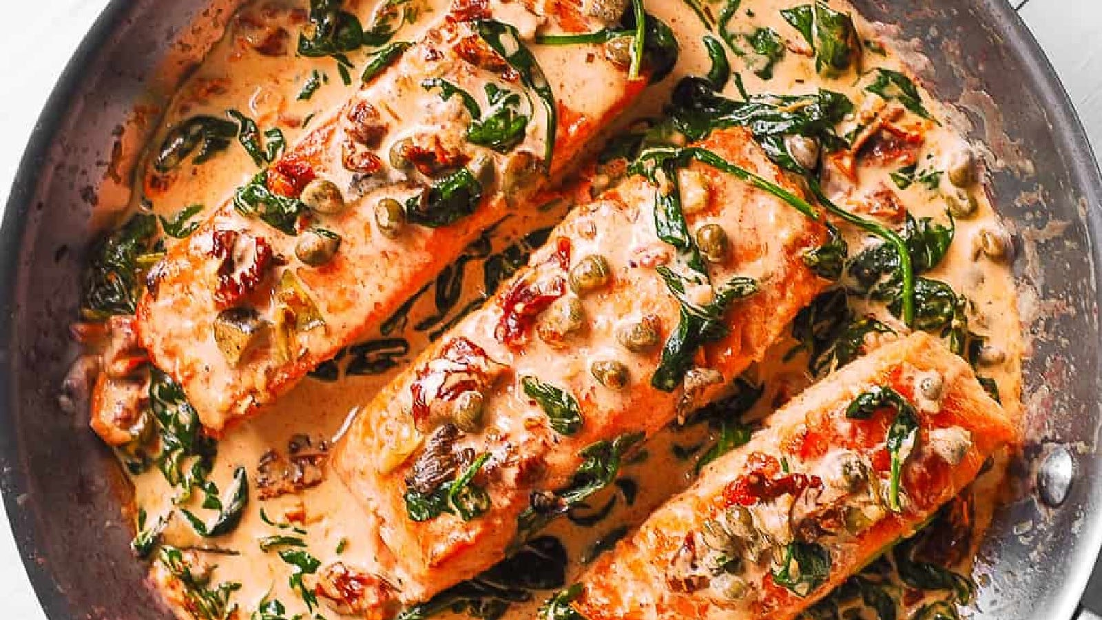 A skillet filled with a few salmon fillets in a Tuscan cream sauce filled with spinach, artichoke, sundried tomato, and capers.