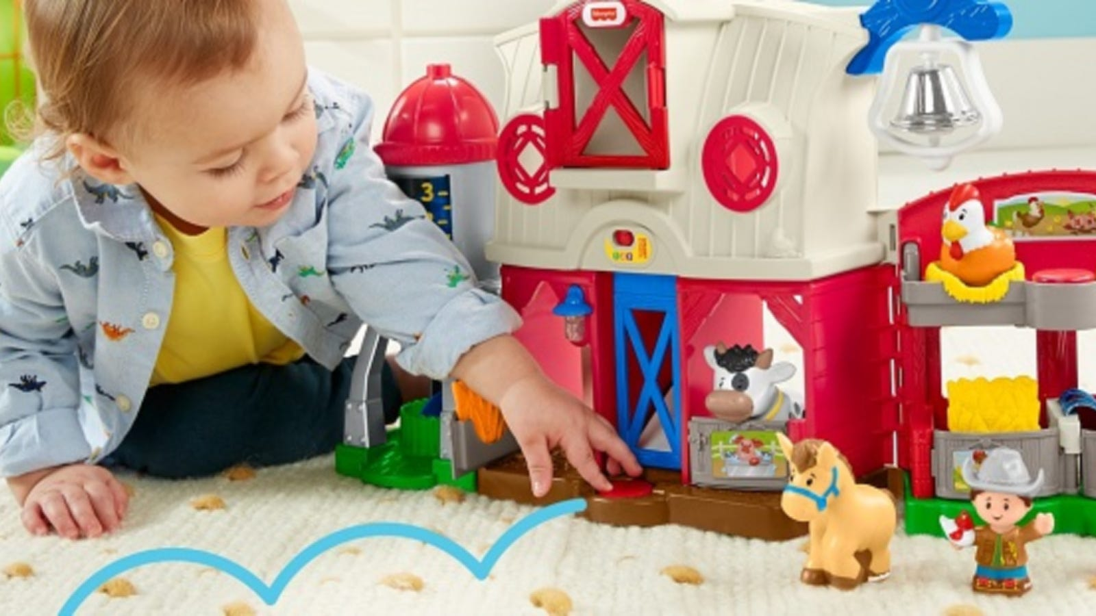 A young toddler playing with a Fisher Price barn set with farm animals.