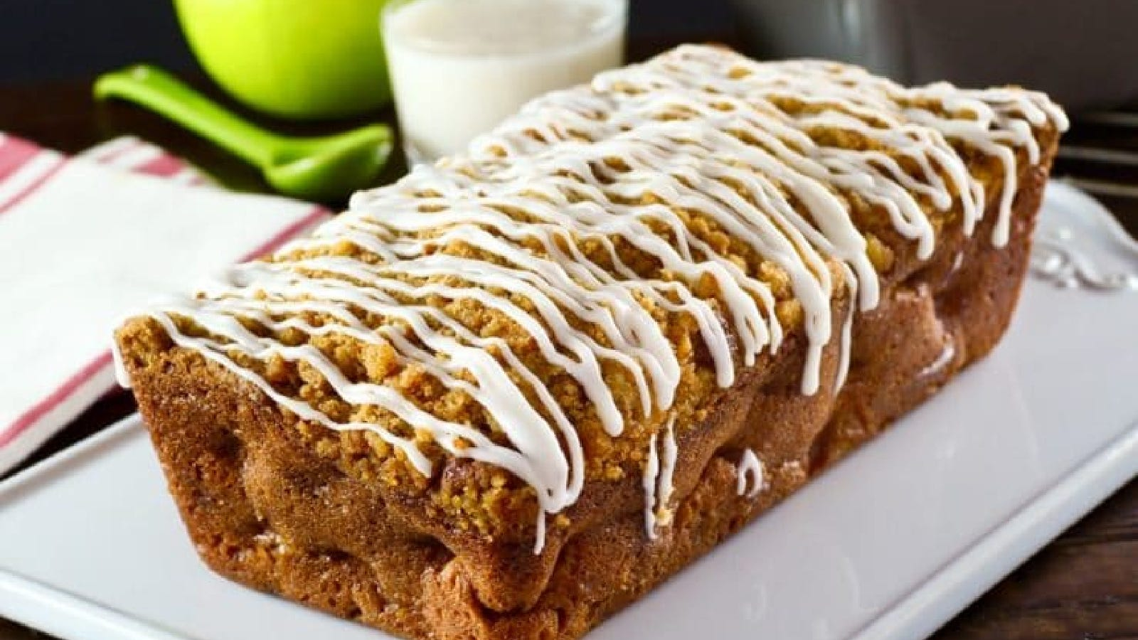 A loaf of apple streusel cake topped with crème glaze, with a glass of milk in the background.