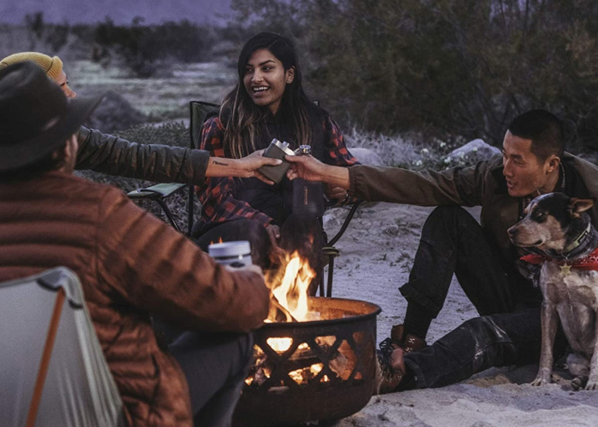 Several people around a campfire sharing a flask