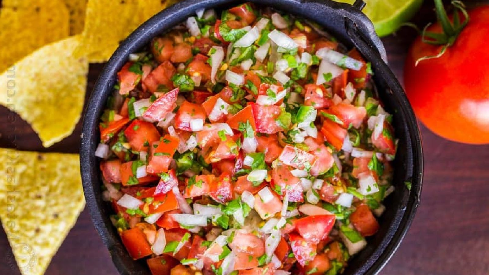 A bowl full of Pico De Gallo with chips, tomatoes, and lime on the side.