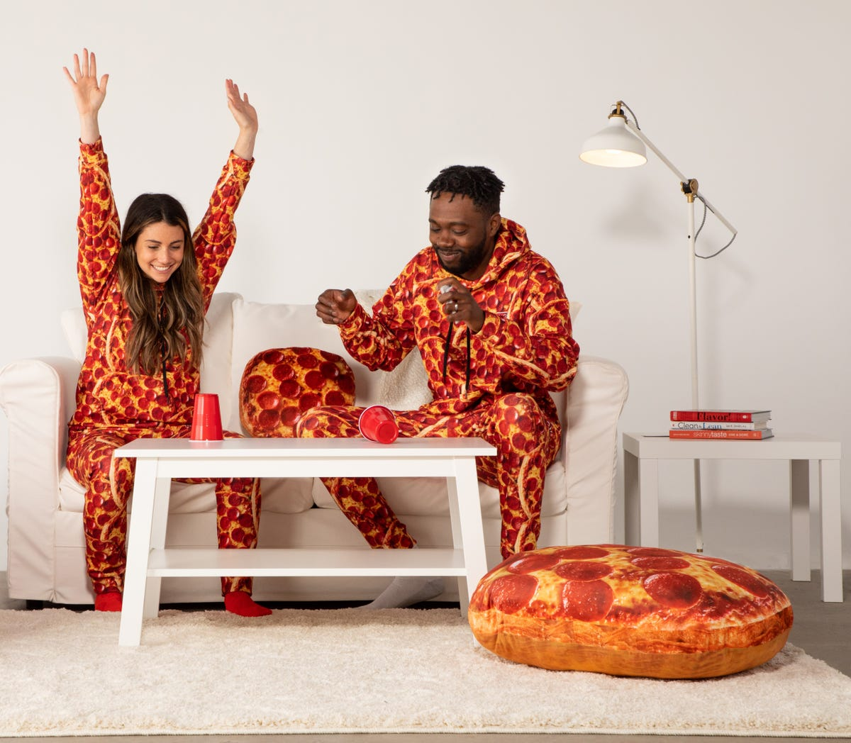 A man and woman sitting on a couch in pizza-covered jumpsuits.