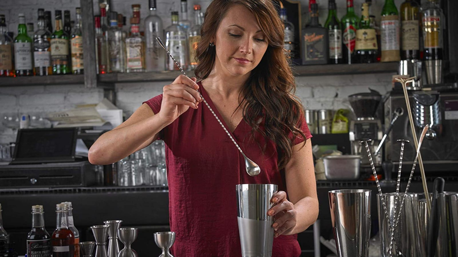 A bartender about to put the bar spoon in a cocktail shaker.