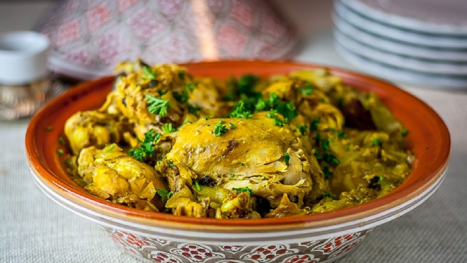 A tagine filled with saffron chicken, with fresh chopped parsley on top.