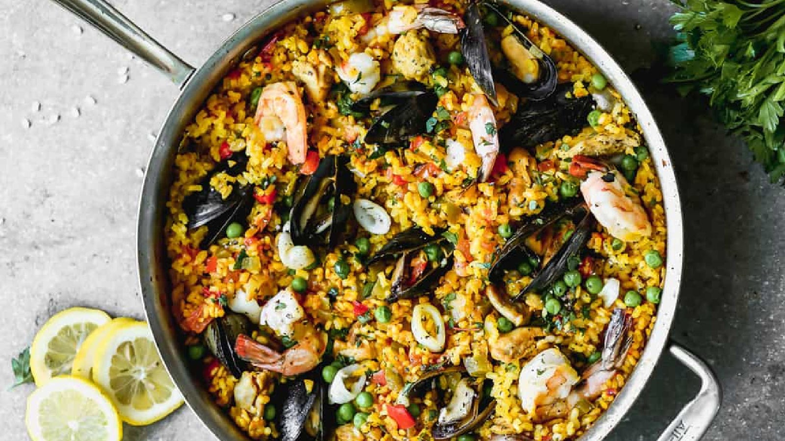 A large deep skillet filled with paella highlighting ingredients like mussels, shrimp, calamari and more.