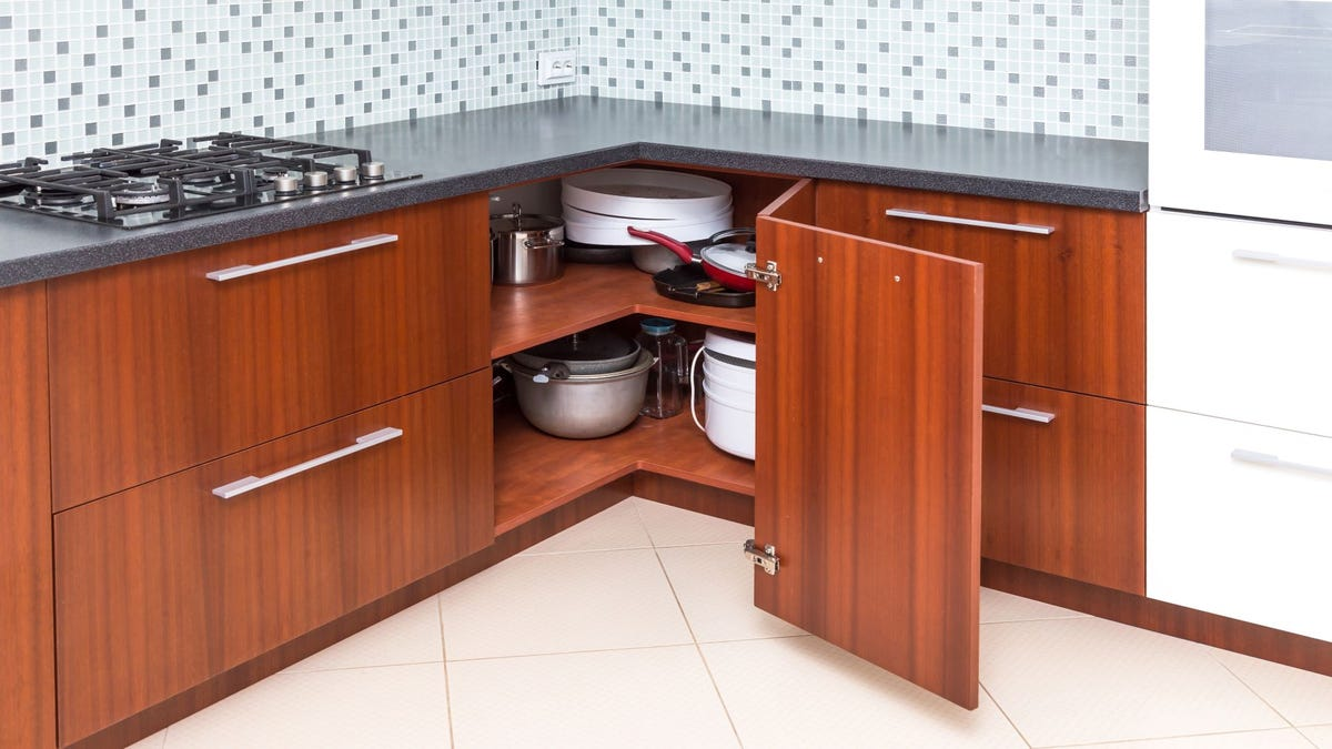 Neatly stacked pots and pans in a bottom corner kitchen cabinet.