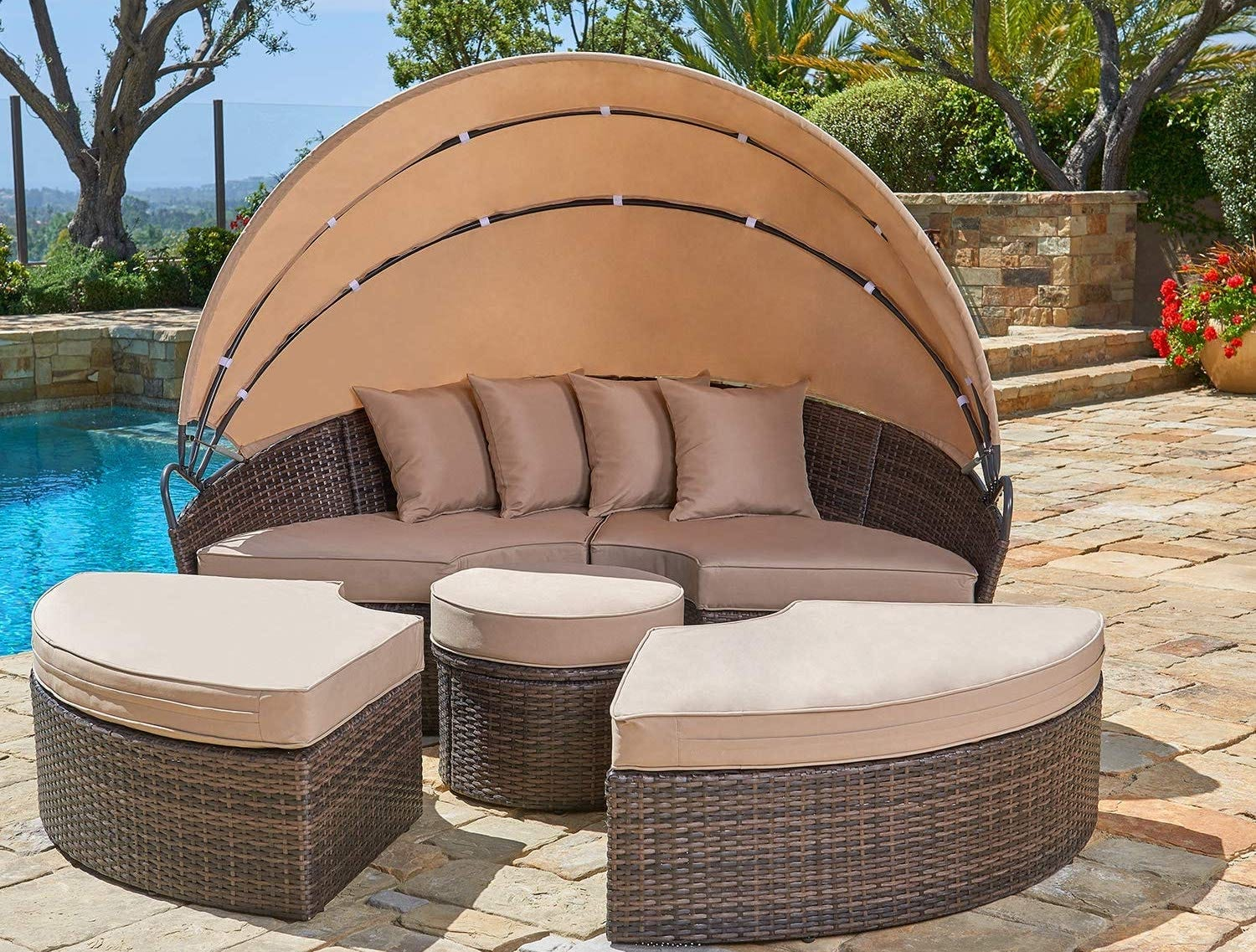 A beige outdoor daybed with a rounded canopy