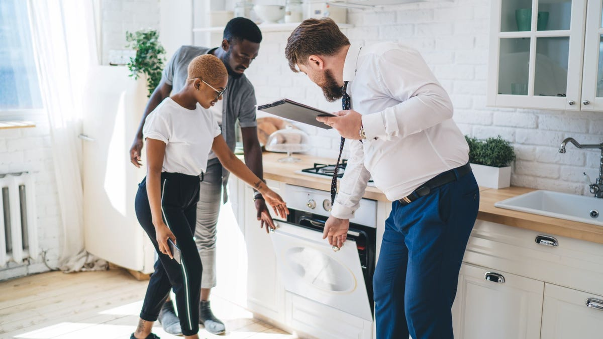 A real estate agent showing a man and woman around a house.