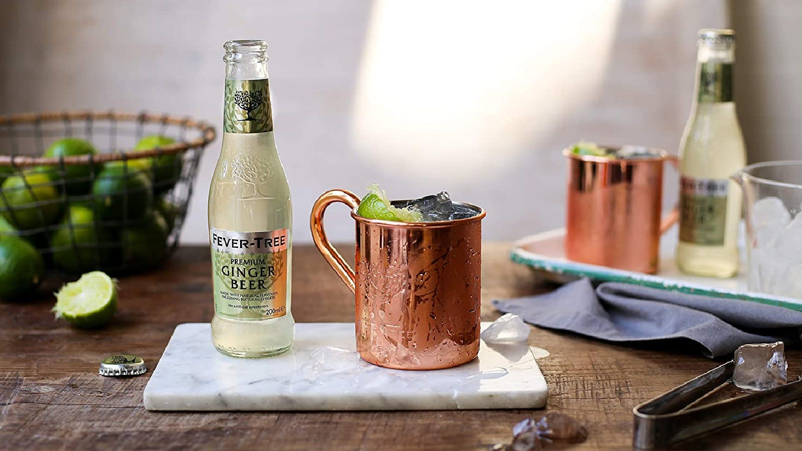 A bottle of Fever Tree ginger beer, along side of a Moscow mule with limes in the background.