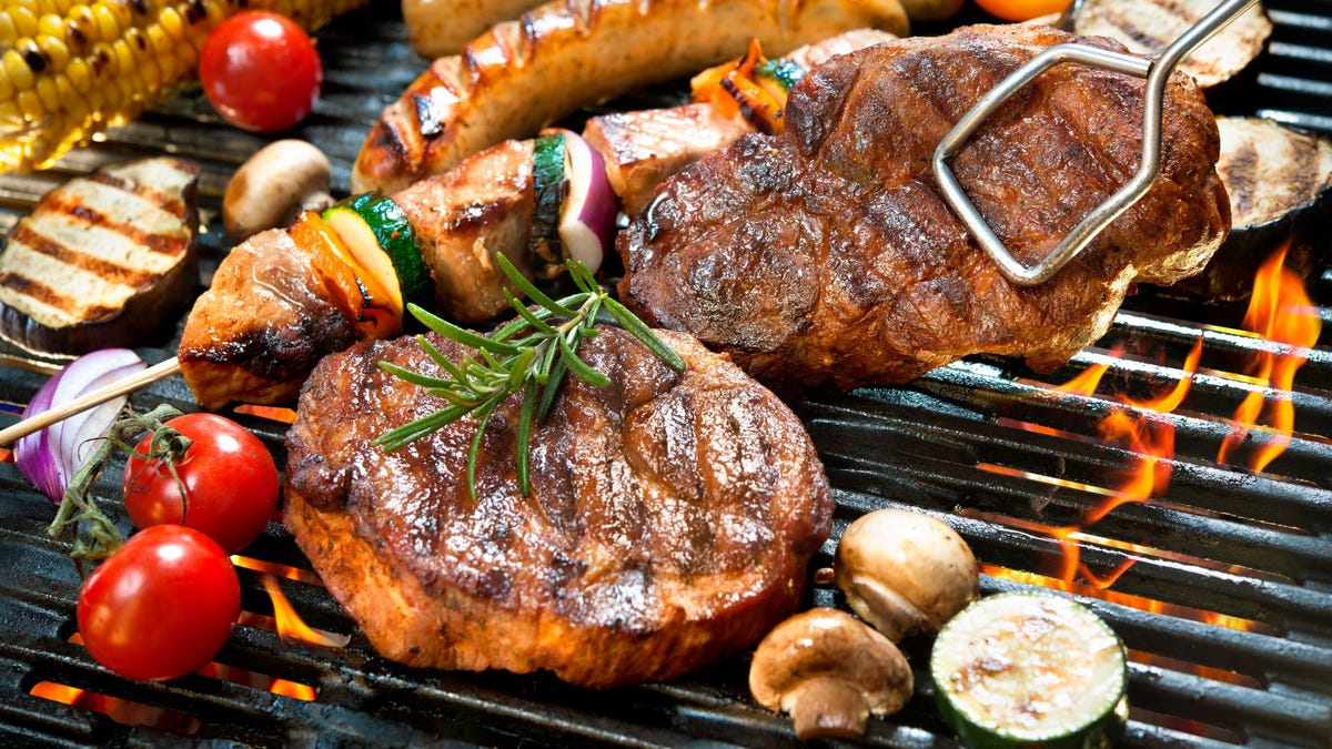 Two steaks and assorted veggies cooking on a grill.