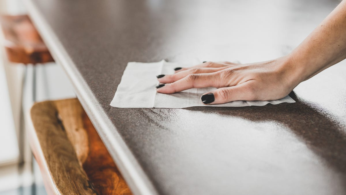 A hand cleaning a bar table with disinfectant wet wipe.