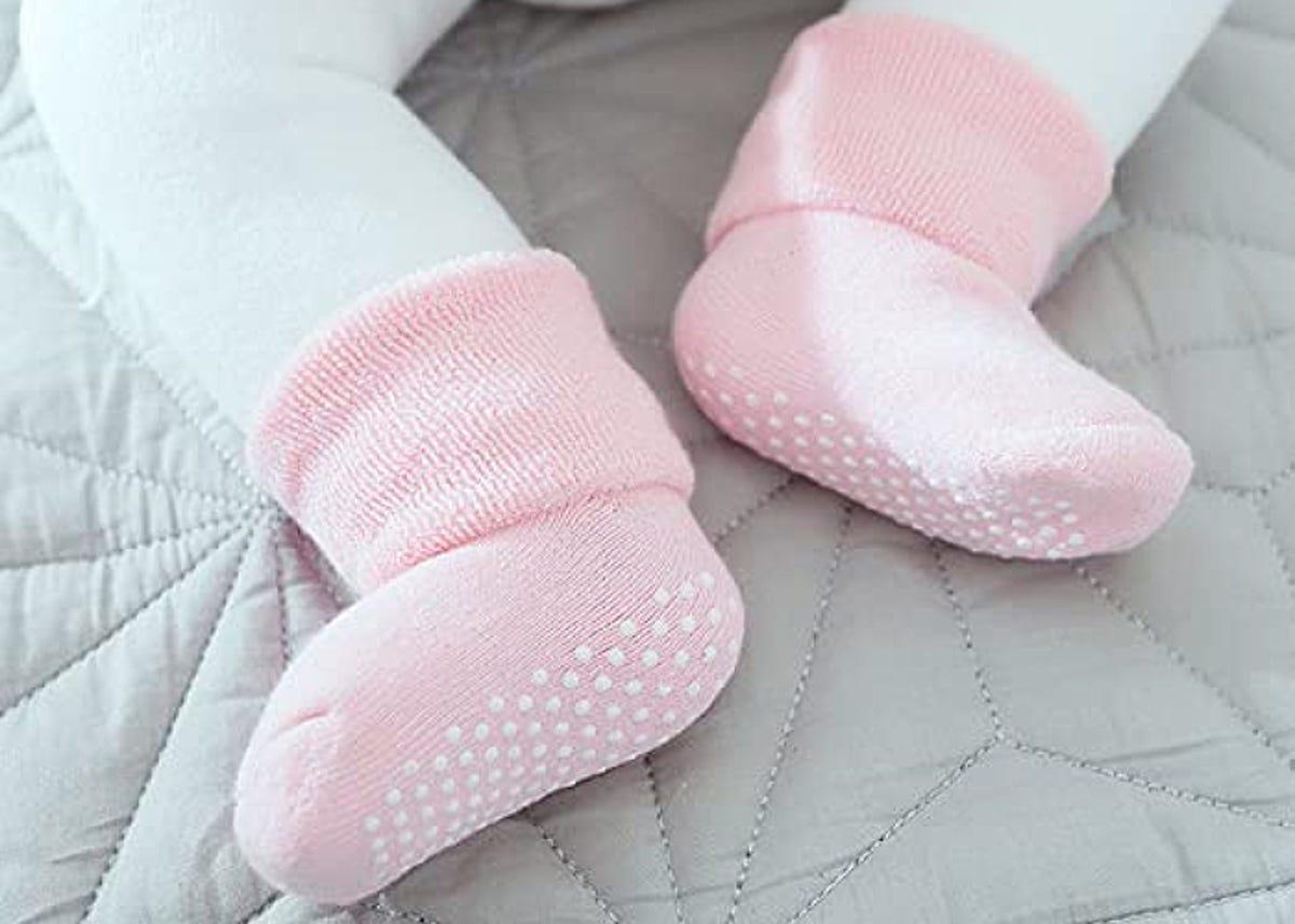 baby feet in little pink socks on gray bedding
