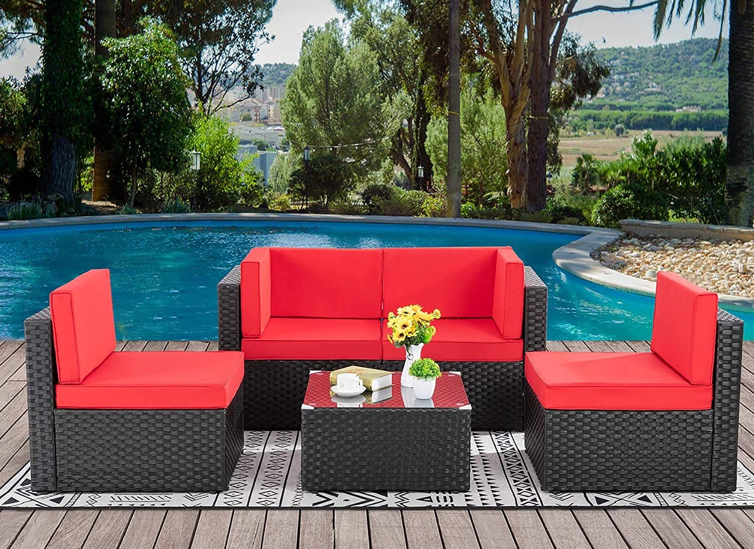 A red outdoor seating area with a sofa, two chairs, and a small table, all in front of a pool