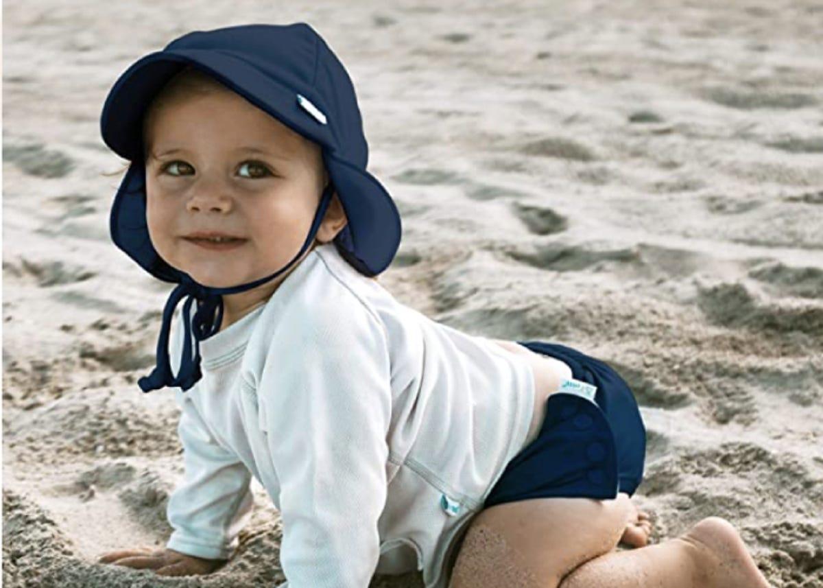 baby boy in a sunhat on the beach
