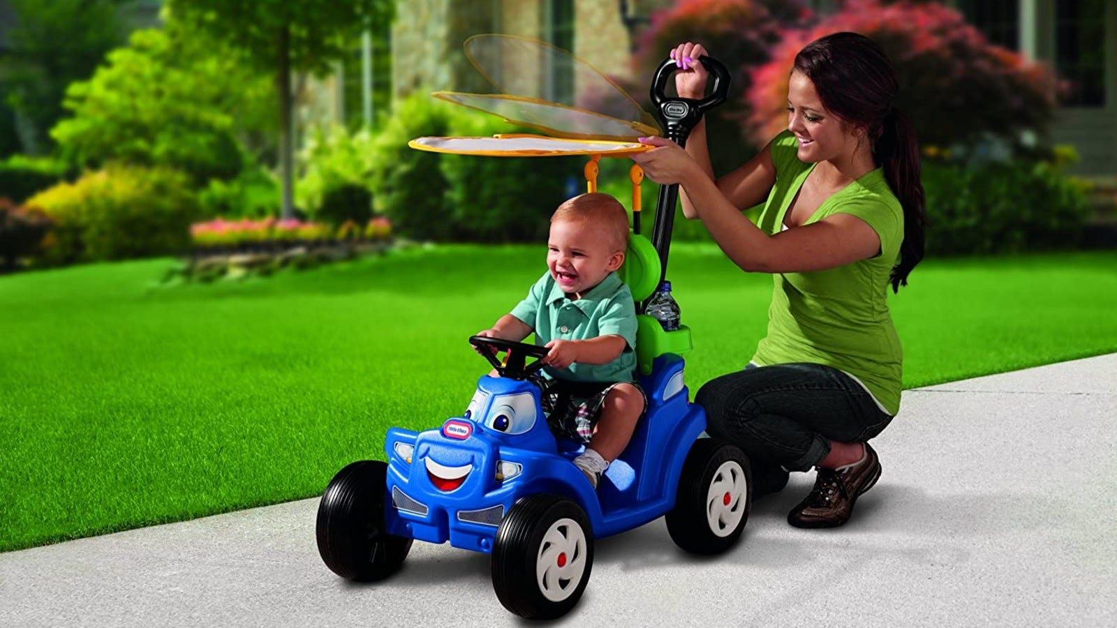 A mom pushing her son in a blue push car with a little face on the front and a canopy over the baby for shade.