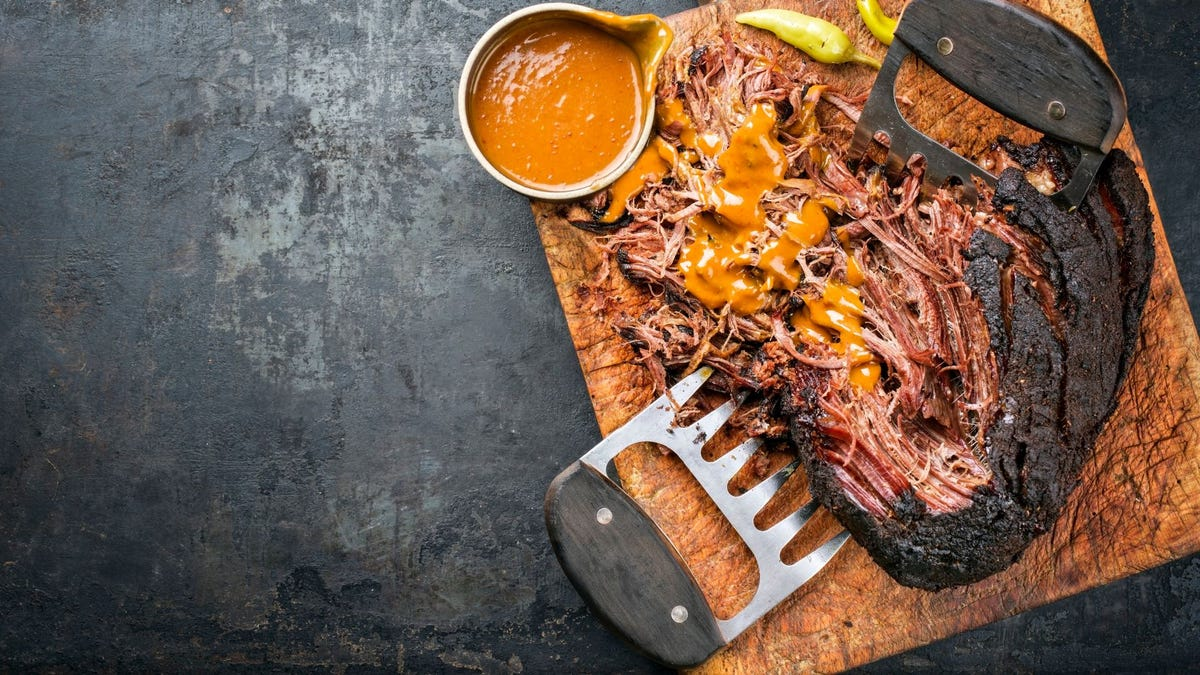Barbecue and sauce on a cutting board.
