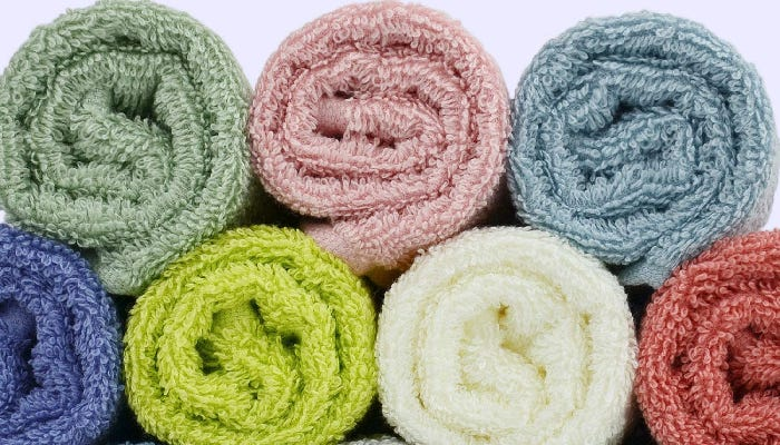 Seven rolled washcloths are stacked and displayed against a white background. The featured image offers a closeup picture of the washcloths' texture.