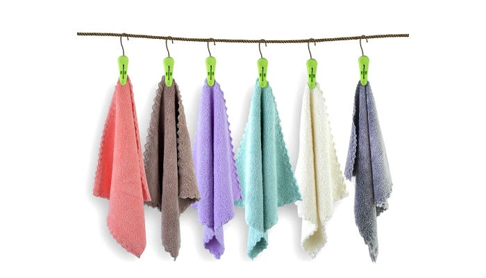 Six washcloths of various colors hang from green hooks on a rod against a white background.