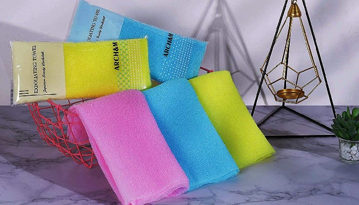 Pink, blue, and yellow washcloths are displayed folded in a case with packaged washcloths behind them. The items are on a counter along with other decorative items.