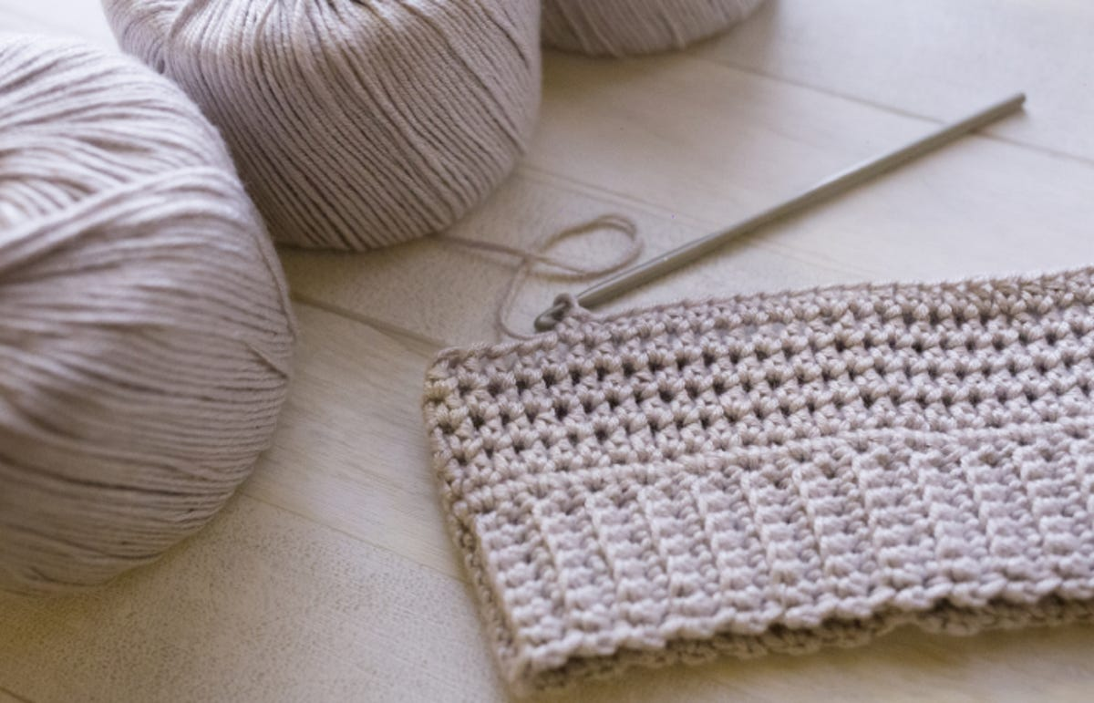 grey cotton yarn next to crochet project in progress on a table