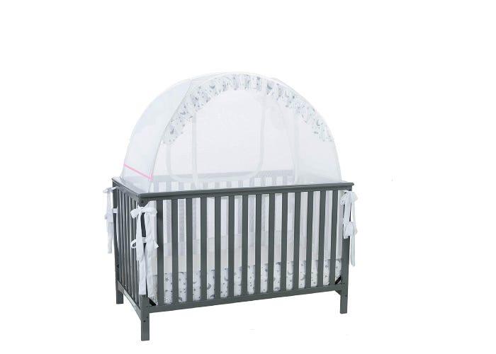 white mesh crib tent displayed on dark gray crib