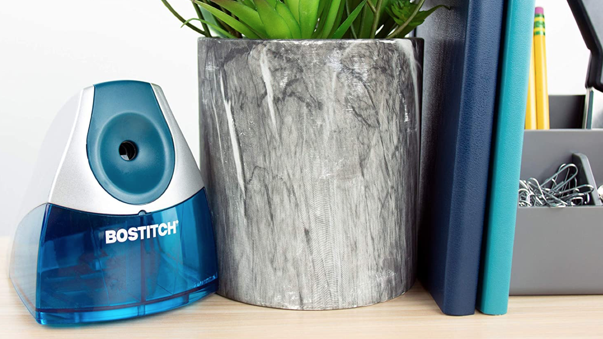 compact blue and white electronic pencil sharpener on a wooden desk beside a plant, several notebooks, and other office supplies
