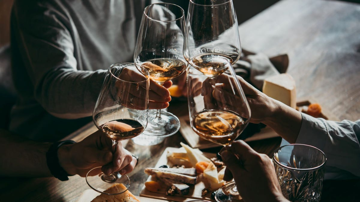 Four people toasting with glasses of wine over a cheese platter.