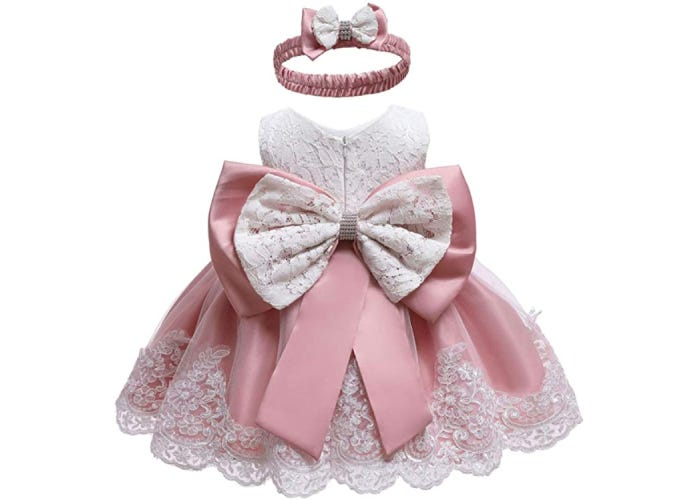 the back of a baby dress made with pink satin and white lace with a big bow and a matching headband