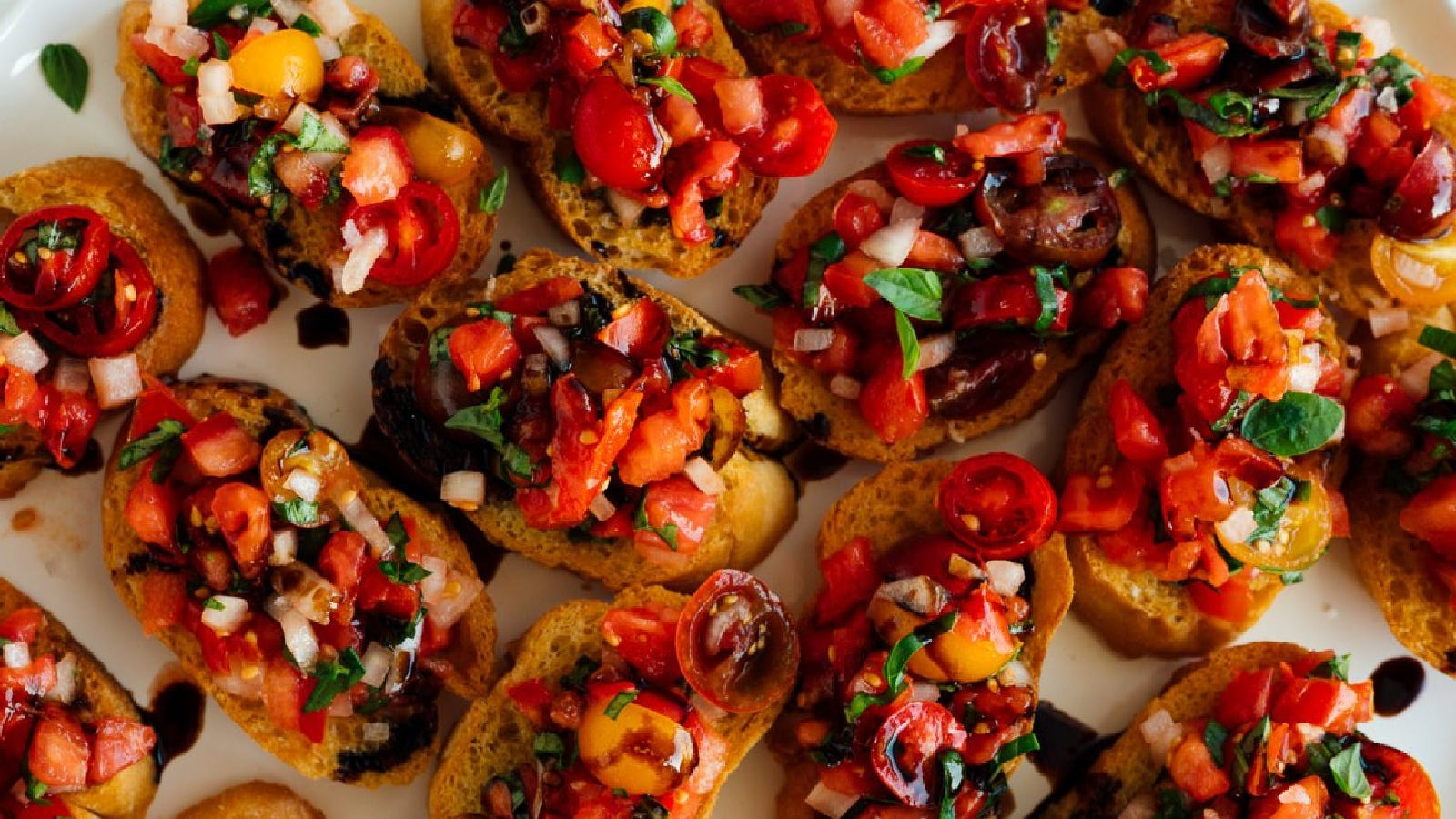 Scattered crostini's, topped with freshly made bruschetta and drizzled with a balsamic reduction.