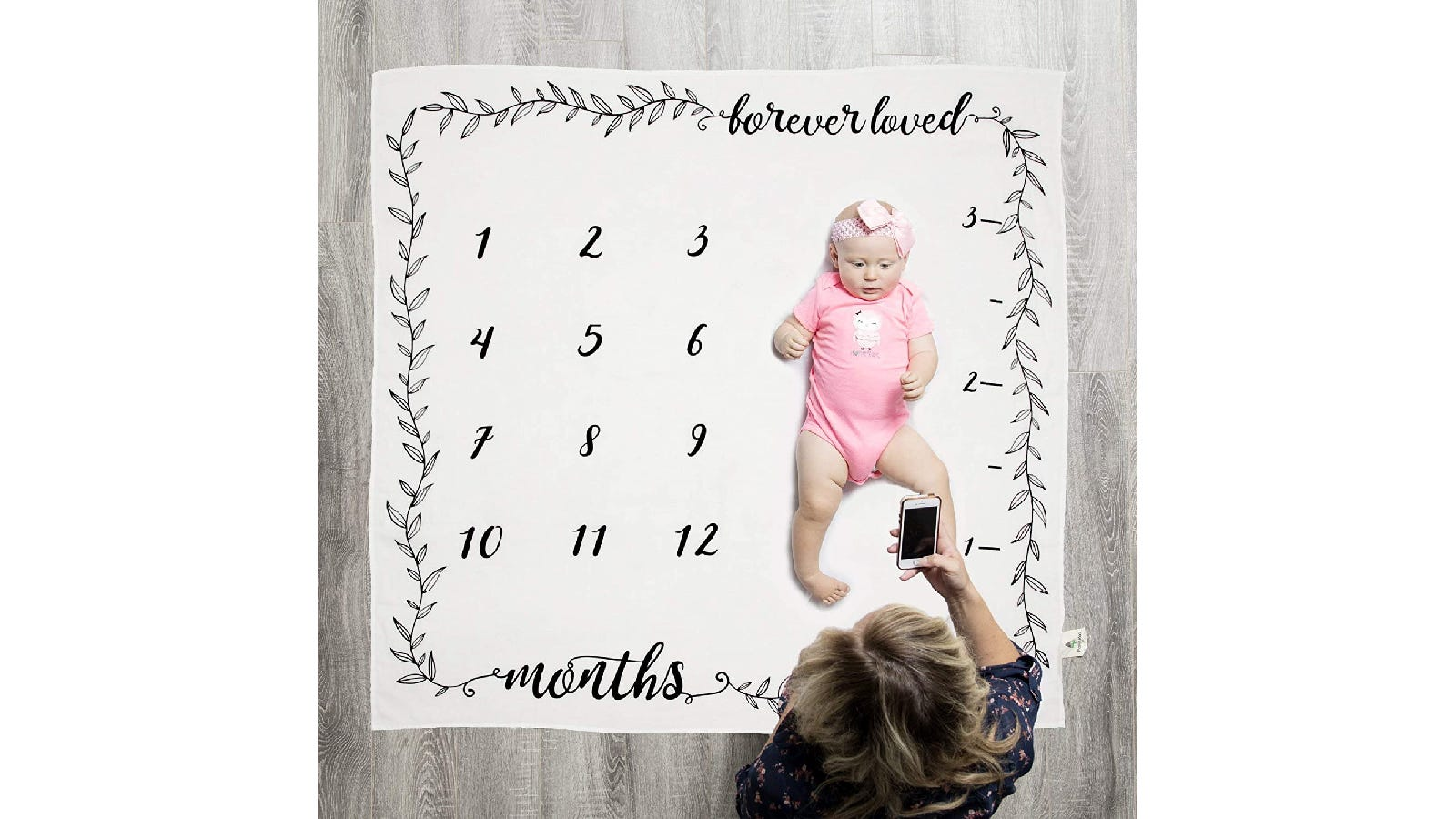 """A baby laying on a white blanket with a black leaf border, the text """"forever loved"""" printed in the top right corner, the numbers 1 through 12 on the left of the blanket, a 3' growth chart on the right of the blanket, and the text """"months"""" printed in the left corner; a woman leans over the baby and takes a picture with her phone."""