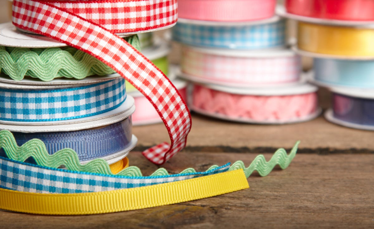 ribbons of various colors and designs stacked on a table