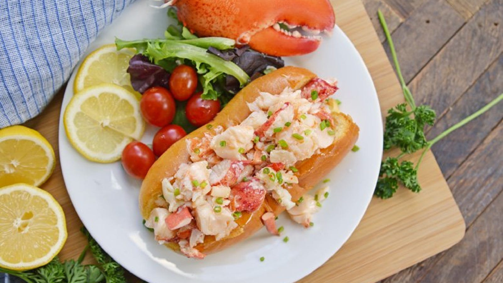 A Connecticut-style lobster roll topped with chives, on a plate with greens, cherry tomatoes, and lemon wheels.