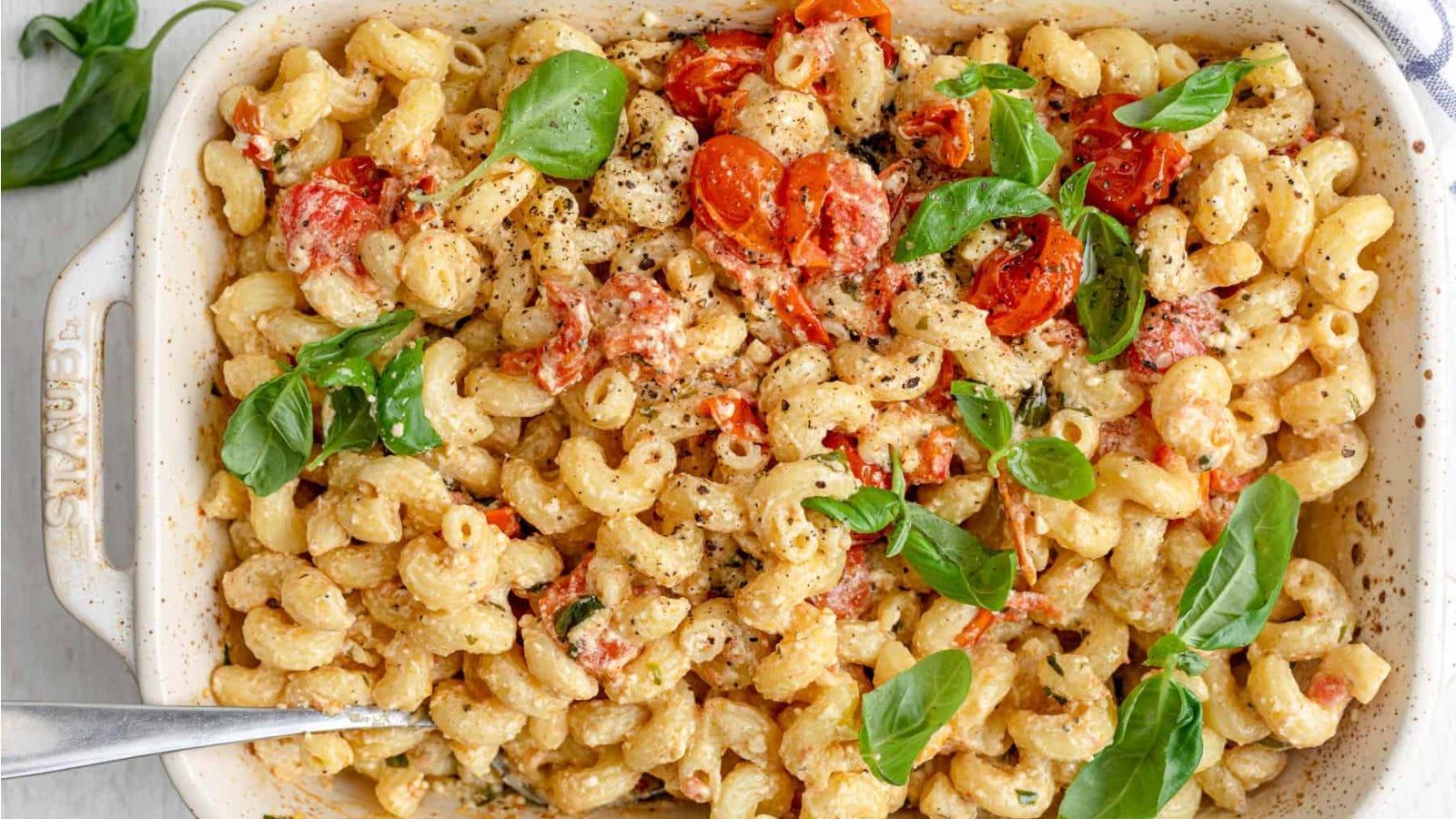 A large Staub casserole dish, filled with cavatappi pasta, fresh basil and cherry tomatoes.