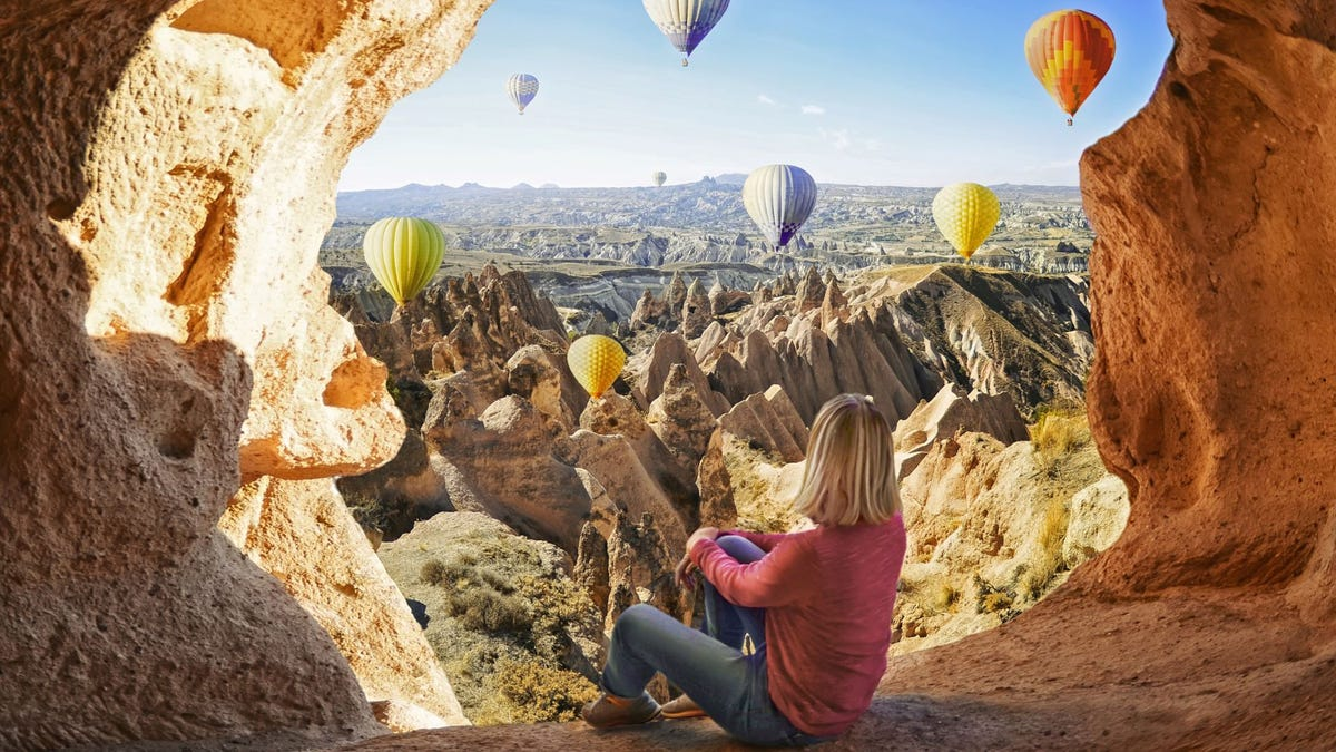 A woman sitting in a cave watching hot air balloons.