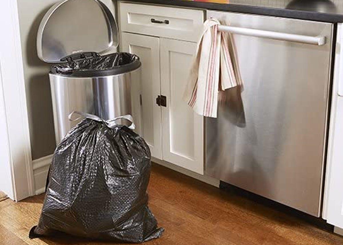 A full black garbage bag beside garbage can in kitchen.