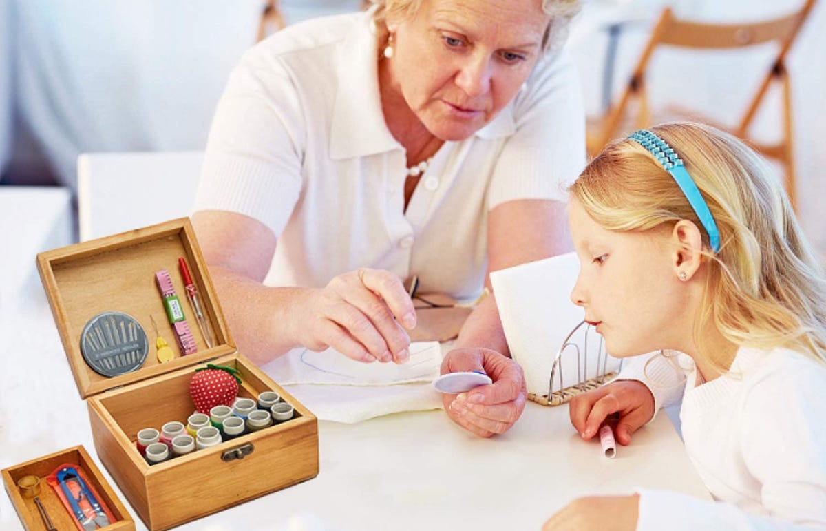 a woman showing her granddaughter how to sew with items from a sewing kit in a box