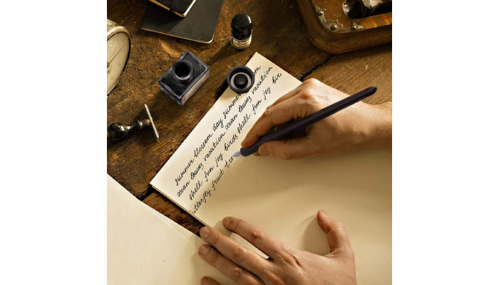 A person writing with the calligraphy pen on a piece of paper.