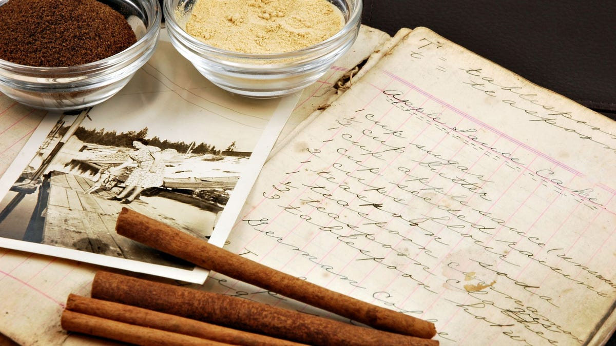 Cinnamon sticks, two bowls of ground herbs, and an old photograph sitting on a handwritten recipe.