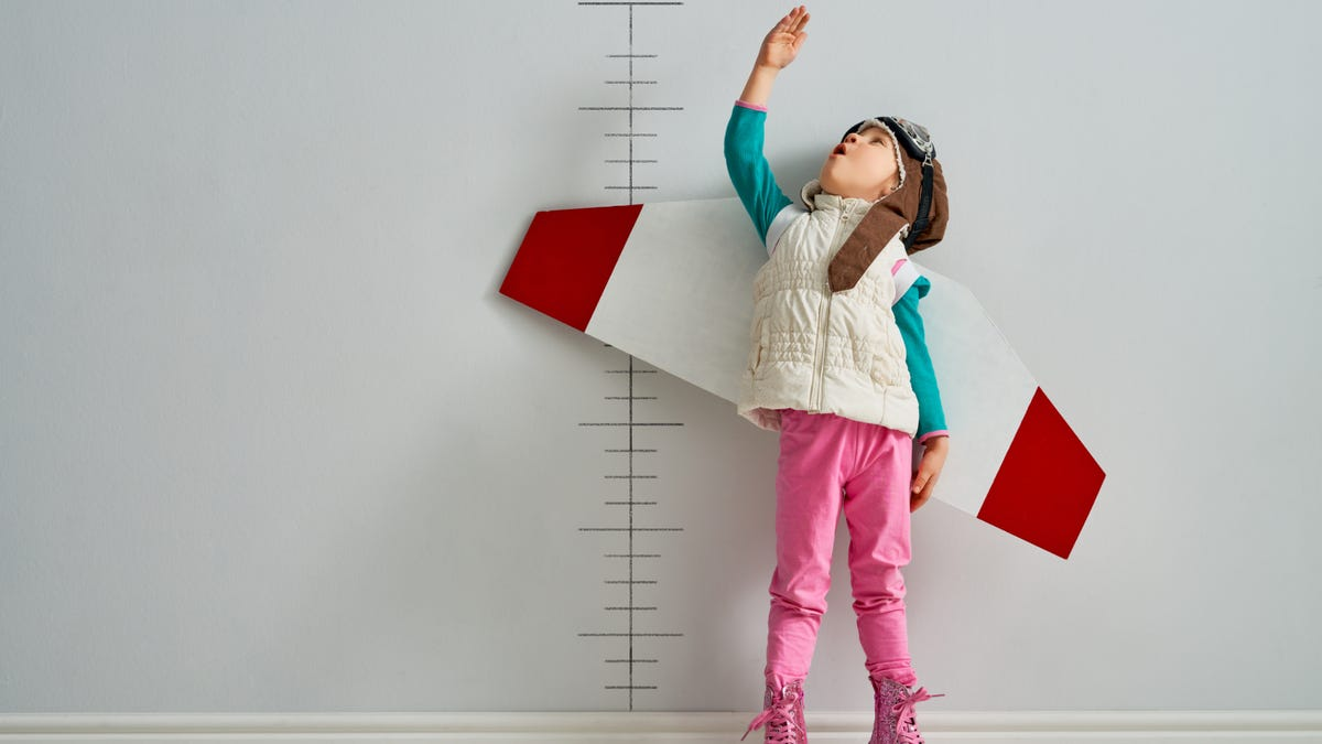 Little child is dressed up as a pilot and measuring their growth on the background of the wall.