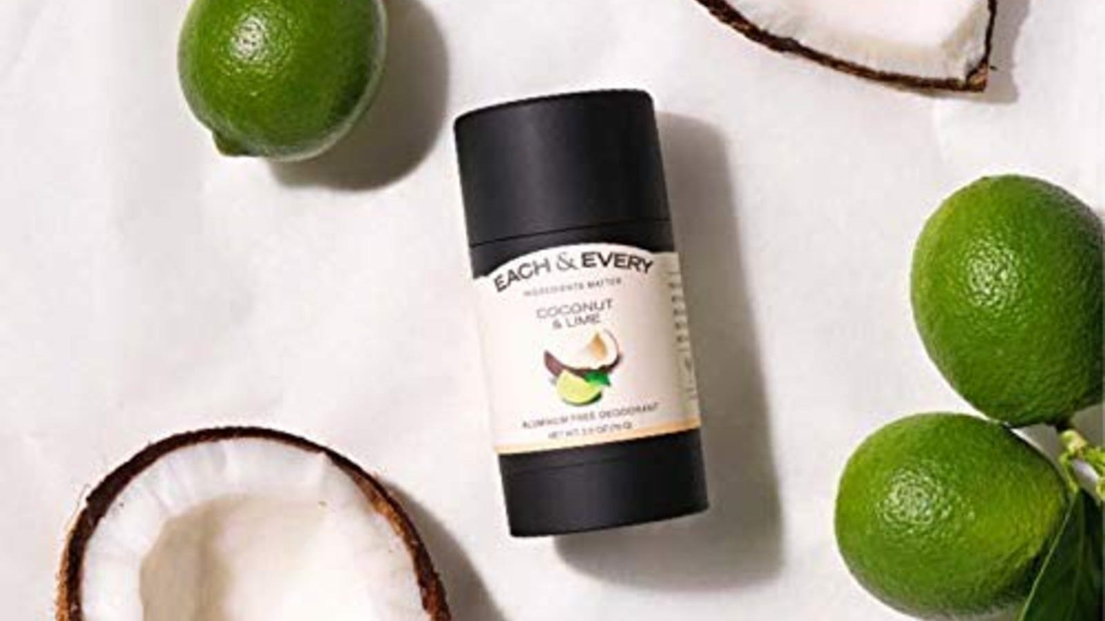 each and every deodorant in black and white packaging on white background with limes and coconuts around it